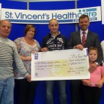John Summers (Centre) alone with his father John, Wife Frances, daughter Holly and sister Joan present his fundraising proceeds to John Hickey